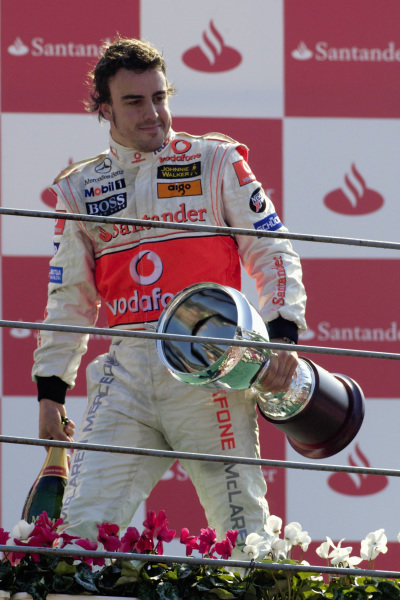 Winner Fernando Alonso leaves the podium with his trophy and bottle of champagne.