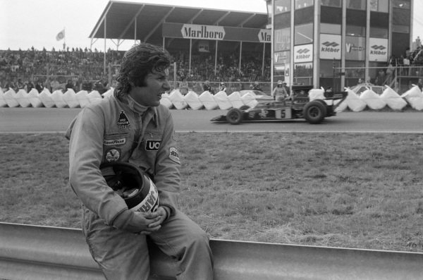 Ronnie Peterson, Lotus 72E Ford, passes Jean-Pierre Jarier watching the action from trackside.