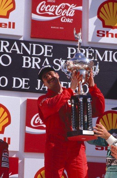 1989 Brazilian Grand Prix.Jacarepagua, Rio De Janeiro, Brazil.24-26 March 1989.Nigel Mansell (Ferrari) can bearly lift his trophy after his 1st position on his Ferrari debut, on the podium. Ref-89 BRA 08.World Copyright - LAT Photographic