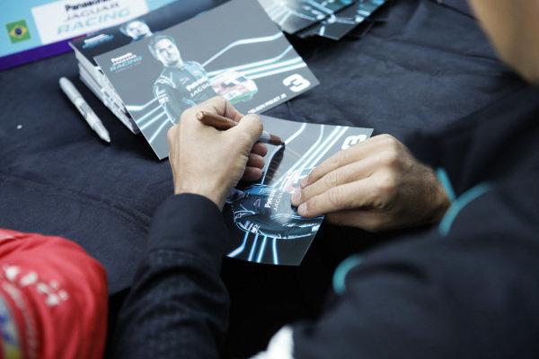 Nelson Piquet Jr. (BRA), Panasonic Jaguar Racing, signs an autograph card