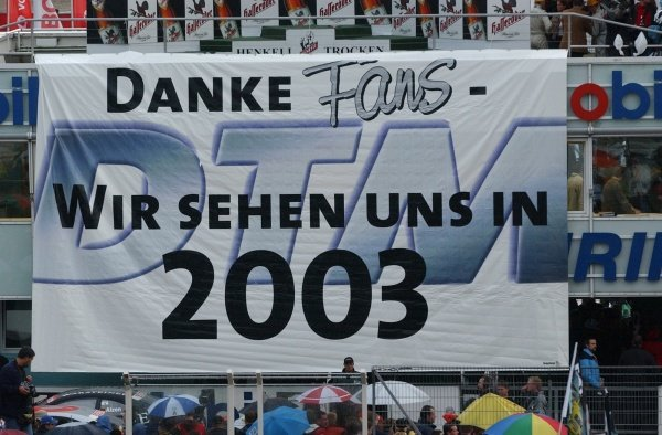 """DTM Championship 2002, Round 10 - Hockenheimring, Germany, 6 October 2002 - Drivers and teams thank the fans by unfolding a big banner with the message """"Thanks fans, we'll see each other again in 2003""""."""