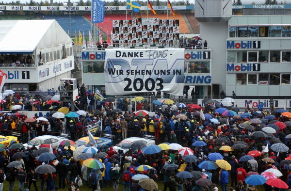 "DTM drivers and teams thank the fans by unfolding a big banner with the message ""Thanks fans, we'll see each other again in 2003"".