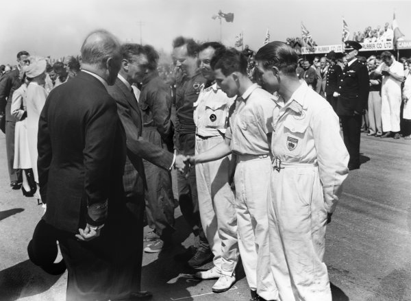 Silverstone, Great Britain. 13th May 1950. King George VI meets the drivers, including a young Stirling Moss, who finished in 2nd position in the 500cc support race, portrait. World Copyright: LAT Photographic Ref: Autocar Glass Plate C26654