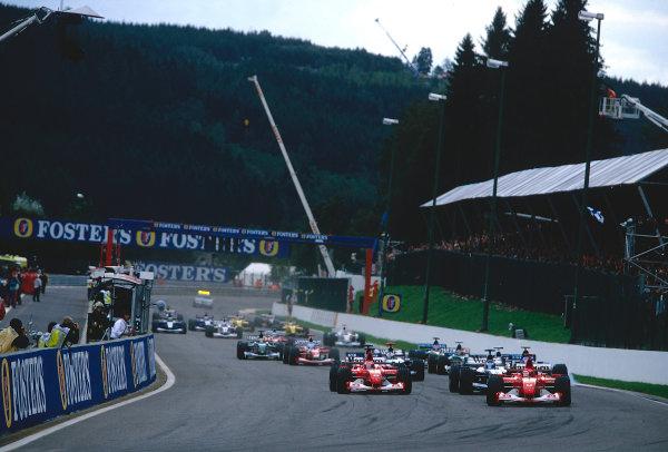 2002 Belgian Grand Prix. Spa-Francorchamps, Belgium.  30/8-1/9 2002. Michael Schumacher followed by Rubens Barrichello (both Ferrari F2002's), Kimi Raikkonen (McLaren MP4/17 Mercedes), Ralf Schumacher, Juan-Pablo Montoya (both Williams FW24 BMW's), Jarno Trulli (Renault R202) and David Coulthard (McLaren MP4/17 Mercedes) into La Source Hairpin at the start. Ref-02 BEL 01. World Copyright - Coates/LAT Photographic