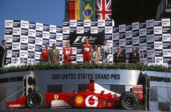 Rubens Barrichello, 1st position, Michael Schumacher, 2nd position, and David Coulthard, 3rd position, on the podium. Barrichello's Ferrari F2002 is being raised.