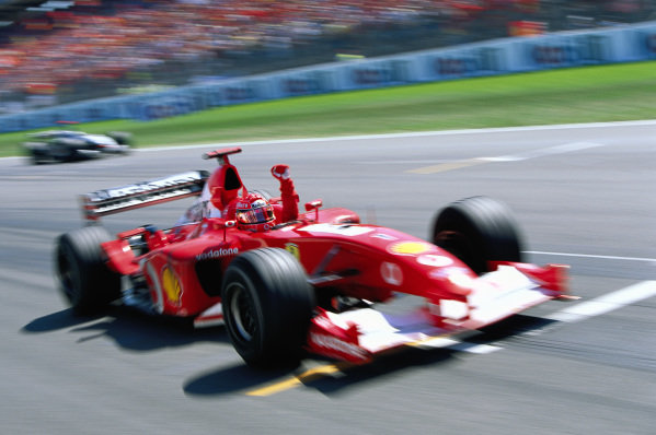 Michael Schumacher, Ferrari F2002, celebrates as he crosses the finish line.
