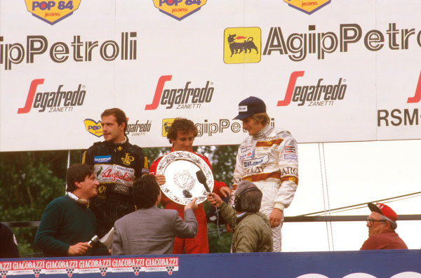 Imola, Italy. 3-5 May 1985. Alain Prost (McLaren TAG Porsche) 1st position but later disqualified due to the car being under weight at the finish, Elio de Angelis (Team Lotus) 1st position and Thierry Boutsen (Arrows BMW) 2nd position, on the podium. Ref-85 SM 03. World Copyright - LAT Photographic