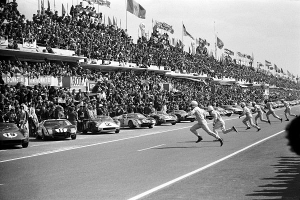Drivers sprint for their cars at the start. Nearest to camera John Surtees runs to his Ferrari 3330P (no.19) on pole position and Richie Ginther runs to his Ford GT40 Mk.1 (no.11).