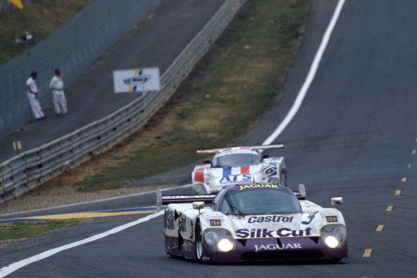 Le Mans, France. 16th - 17th June 1990. John Nielsen/Price Cobb/Eliseo Salazar/Martin Brundle (Jaguar XJR-12), 1st position, leads Richard Piper/Olindo Iacobelli/Mike Youles (Spice SE89C Ford), 21st position, action.  World Copyright: LAT Photographic. Ref:  90LM