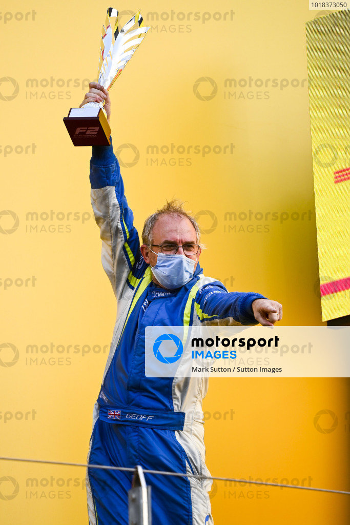 Winning Constructor Representative celebrates on the podium with the trophy