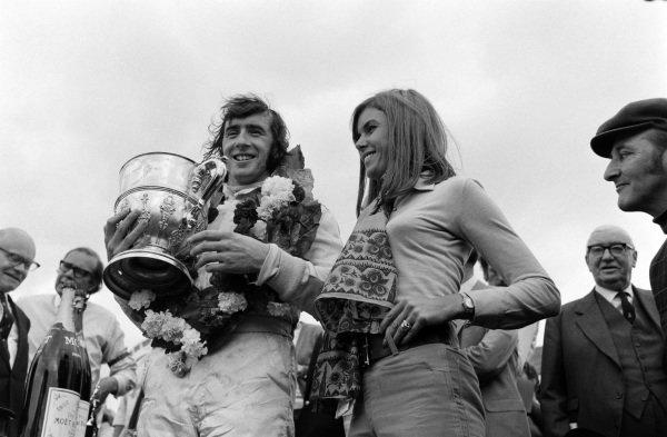 Race winner Jackie Stewart on the podium with wife Helen.
