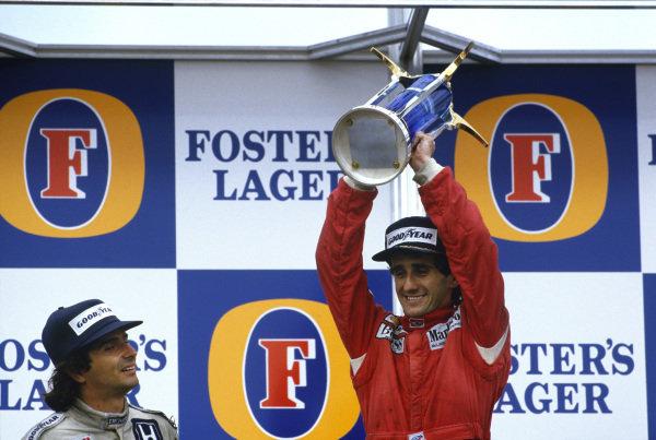 1986 Australian Grand Prix. Adelaide, Australia. 24th - 26th October 1986. Alain Prost (McLaren TAG Porsche) 1st position, celebrates becoming World Champion again with Nelson Piquet (Williams Honda) 2nd position on the podium, portrait. World Copyright: LAT Photographic. Ref: 86AUS
