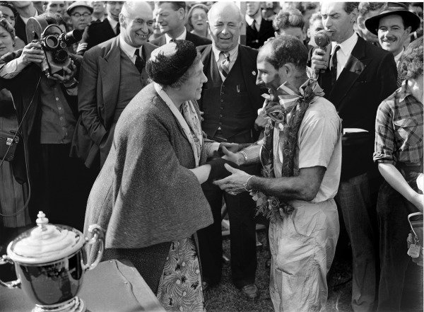 Aintree, England. 18-20 July 1957.Stirling Moss (Vanwall), 1st position, being congratulated by Aintree's owner, Mrs Mirabel Topham with Earl Howe, President of the BRDC, looking on, portrait.World Copyright: LAT Photographic.Ref: Autocar Glass Plate C49681.