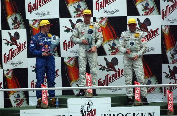 DTM Championship 2002, Round 10 - Hockenheimring, Germany, 6 October 2002 - Podium of the last race of the 2002 season. 1st: Bernd Schneider (GER),Vodafone AMG-Mercedes, centre; 2nd: Mattias Ekstrom (SWE), Team Abt, left; 3rd: Uwe Alzen (GER), Warsteiner AMG-Mercedes, right.DTM Championship, Rd10, Hockenheim, Germany. 06 October 2002.DIGITAL IMAGE