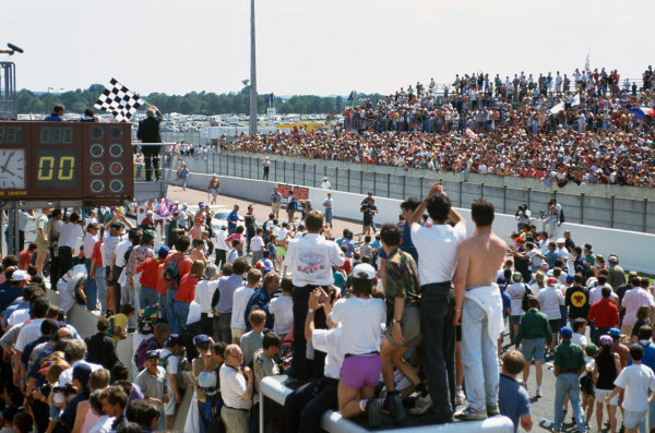 1993 Le Mans 24 Hours. Le Mans, France. 19th - 20th June 1993. The chequered flag is waved as the crowd serge onto the track, atmosphere. World Copyright: LAT Photographic. Ref:  93LM23