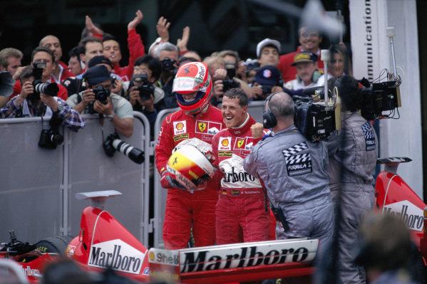 Michael Schumacher celebrates victory alongside Ferrari teammate Eddie Irvine in parc ferme.