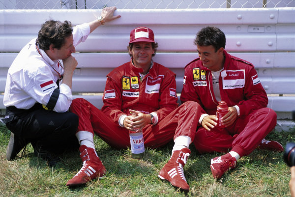 Teammates Gerhard Berger and Jean Alesi chat trackside with team boss Jean Todt before the race.