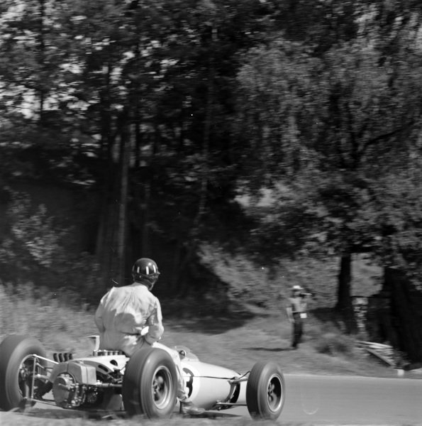 Innes Ireland, BRP 1 BRM, gives Graham Hill a lift back to the pits.