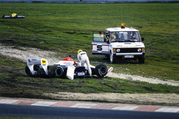 Ayrton Senna gets out of his wrecked Toleman TG184 Hart. He is attended to by marshals.