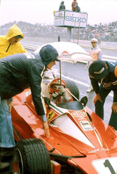 Niki Lauda, Ferrari 312T2, tries to keep dry as he talks with his mechanics.
