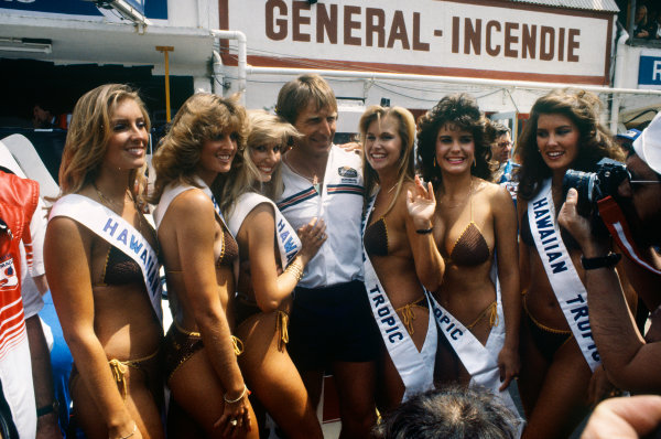 Le Mans, France. 18-19 June 1983.Derek Bell (Porsche 956), 2nd position, with the Hawaiian Tropic girls in the paddock, glamour, portrait. World Copyright: LAT Photographic.Ref:  83LM
