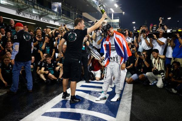 Yas Marina Circuit, Abu Dhabi, United Arab Emirates. Sunday 23 November 2014. Lewis Hamilton, Mercedes AMG, 1st Position, celebrates 2014 title success with his team. World Copyright: Andy Hone/LAT Photographic. ref: Digital Image _ONY2291