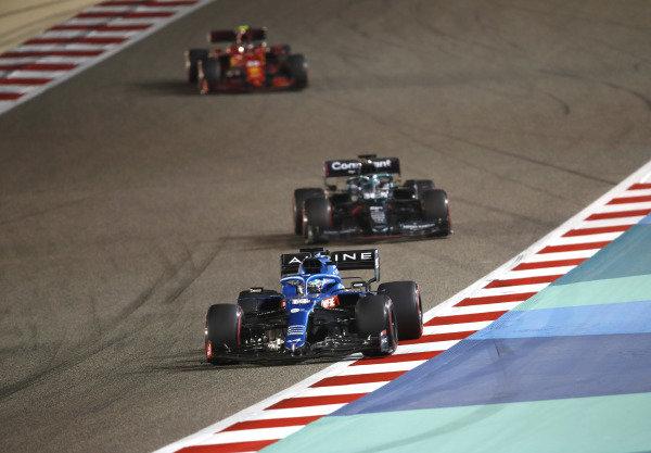 Fernando Alonso, Alpine A521, leads Lance Stroll, Aston Martin AMR21, and Carlos Sainz, Ferrari SF21