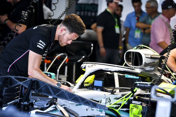 Engineer installing new livery on the halo of Mercedes AMG F1 W10