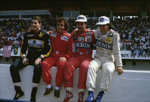 (L-R) Championship contenders Ayrton Senna, Alain Prost, Nigel Mansell and Nelson Piquet sat on the pit wall.