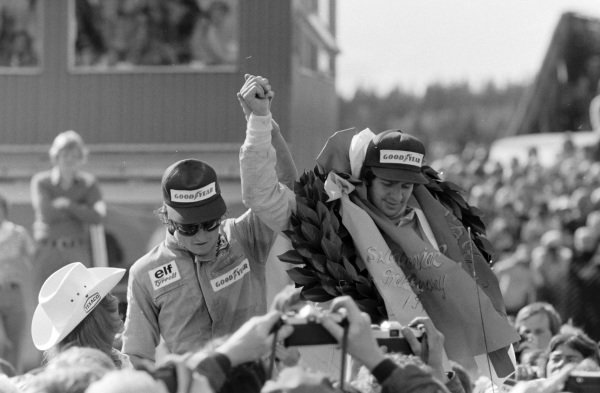 Race winner Jody Scheckter celebrates on the podium with teammate Patrick Depailler, 2nd position.