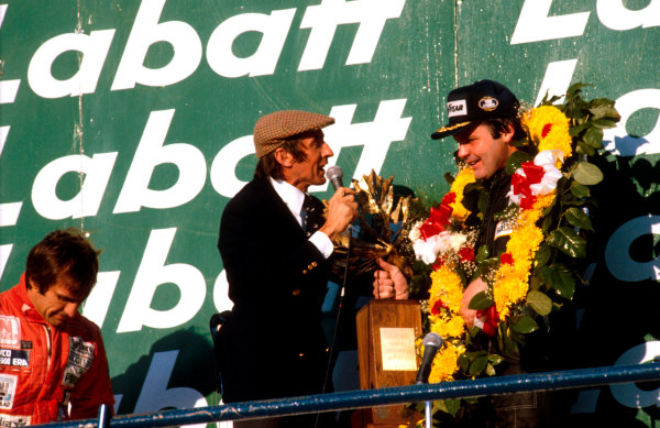 1980 Canadian Grand Prix.Montreal, Quebec, Canada.26-28 September 1980.Alan Jones (Williams Ford) 1st position talks to Jackie Stewart on the podium. Carlos Reutemann (Williams Ford) 2nd position stands behind .Ref-80 CAN 03.World Copyright - LAT Photographic