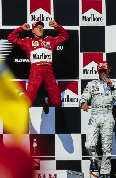 Michael Schumacher, 1st position, leaps in celebration on the podium as he clinches his fourth world drivers' championship. David Coulthard, 3rd position, is alongside.