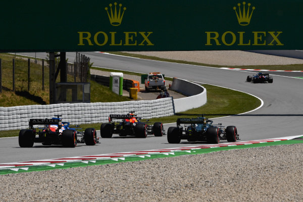 Max Verstappen, Red Bull Racing RB16B, leads Lance Stroll, Aston Martin AMR21, and Fernando Alonso, Alpine A521