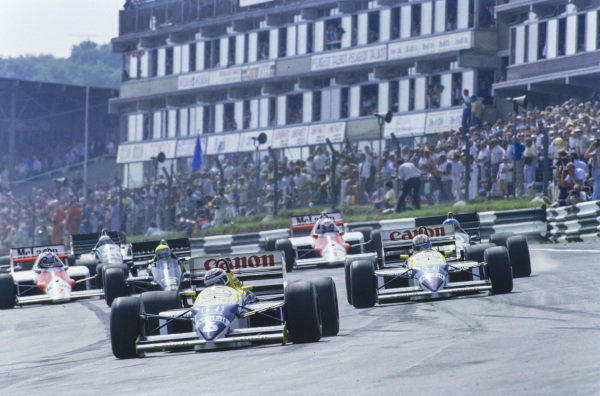 Nelson Piquet, Williams FW11 Honda, leads Nigel Mansell, Williams FW11 Honda, Gerhard Berger, Benetton B186 BMW, and Ayrton Senna, Lotus 98T Renault, at the start.