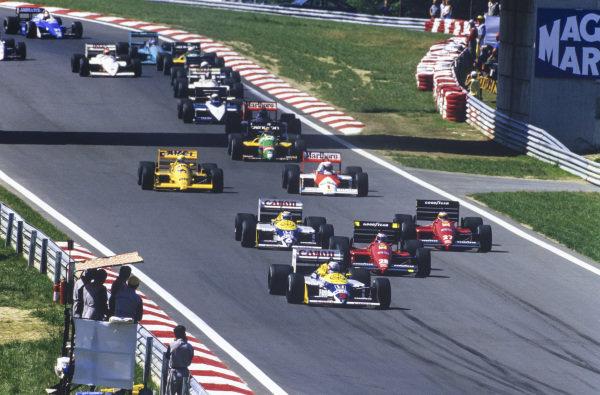 Nigel Mansell, Williams FW11B Honda, leads Gerhard Berger, Ferrari F1-87, Michele Alboreto, Ferrari F1-87, Nelson Piquet, Williams FW11B Honda, Alain Prost, McLaren MP4-3 TAG, Ayrton Senna, Lotus 99T Honda, Thierry Boutsen, Benetton B187 Ford, and Stefan Johansson, McLaren MP4-3 TAG, at the start.