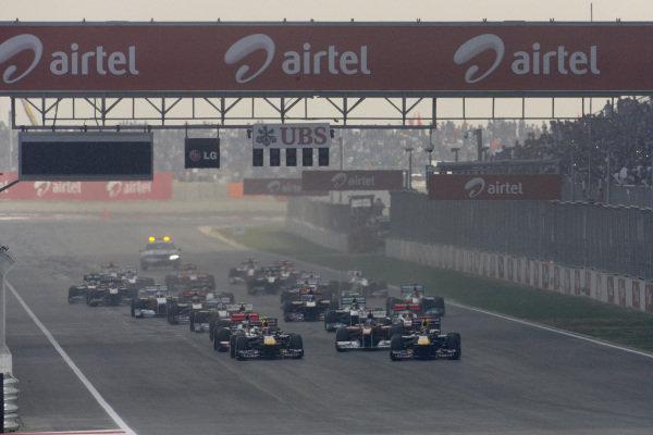 Sebastian Vettel, Red Bull RB7 Renault, leads Mark Webber, Red Bull RB7 Renault, Fernando Alonso, Ferrari 150° Italia, and Jenson Button, McLaren MP4-26 Mercedes, off the line at the start.