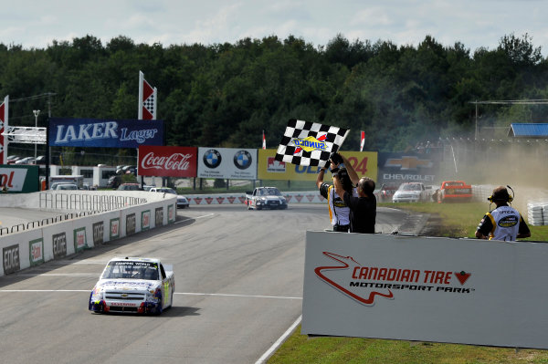 30 August - 1 September 2013, Bowmanville, Ontario Canada Chase Elliott crosses the finish line for the win under the checkered flag as the crash of Ty Dillon is in the background ©2013, Scott R LePage LAT Photo USA