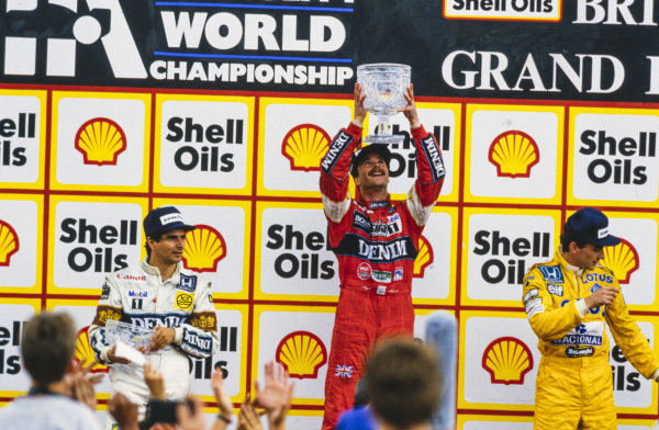 Nigel Mansell, 1st position, raises his trophy on the podium. He is alongside Nelson Piquet, 2nd position, and Ayrton Senna, 3rd position.