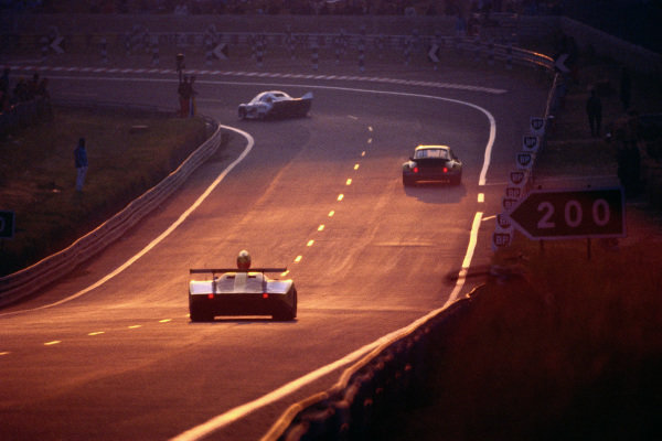 A Renault chases a Porsche at dusk.