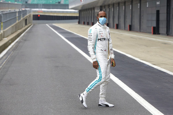 Lewis Hamilton wears a protective face mask in the pit lane as he prepares to drive a Mercedes W09
