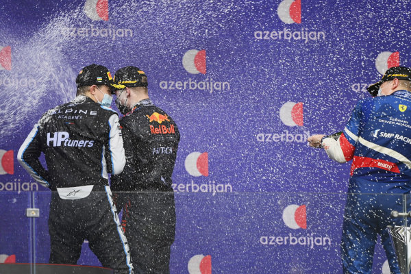 Oscar Piastri (AUS, Prema Racing), 2nd position, Juri Vips (EST, Hitech Grand Prix), 1st position, and Robert Shwartzman (RUS, Prema Racing), 3rd position, spray champagne on the podium