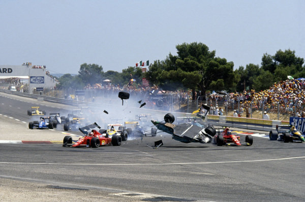 1989 French Grand Prix. Paul Ricard, Le Castellet, France. 7-9 July 1989.  Mauricio Gugelmin (March CG891 Judd) has a huge crash at Epingle Ecole at the start of the race. Nigel Mansell (Ferrari) and Gerhard Berger (Ferrari) pick their way past, as Olivier Grouillard (Ligier-Cosworth) takes to the gravel in the background. Action. World Copyright: Jeff Bloxham/LAT Photographic Ref: 89 FRA 08.
