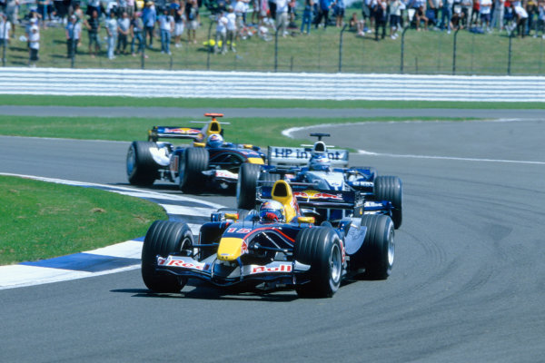 2005 British Grand Prix. Silverstone, England. 8th - 10th July 2005 Christian Klien, Red Bull Racing Cosworth RB1 leads Nick Heidfeld, Williams F1 BMW FW27 and David Coulthard, Red Bull Racing Cosworth RB1. Action. World Copyright: Charles Coates/LAT Photographic Ref: 35mm Image A11