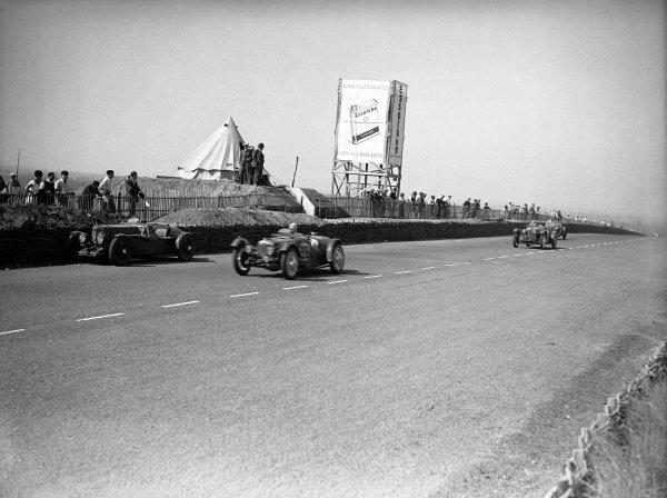 1934 Le Mans 24 hours. Le Mans, France. 16-17 June 1934. A Riley passes the retired Augustus Cesare Bertelli/SC Penn-Hughes Aston Martin Ulster. World Copyright: LAT Photographic Ref: Autocar Glass Plate C4022