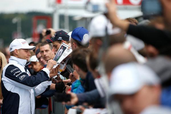 Spa-Francorchamps, Spa, Belgium. Thursday 21 August 2014. Valtteri Bottas, Williams F1, signs autographs for fans. World Copyright: Glenn Dunbar/LAT Photographic. ref: Digital Image _W2Q3830