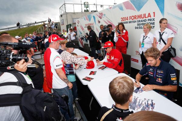 Silverstone, Northamptonshire, England. Saturday 5 July 2014. Kimi Raikkonen, Ferrari, and Sebastian Vettel, Red Bull Racing. sign autographs for fans. World Copyright: Andrew Ferraro/LAT Photographic. ref: Digital Image _FER0368