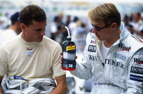 Sepang, Kuala Lumpur, Malaysia. 15-17 October 1999. McLaren Mercedes teammates David Coulthard and Mika Hakkinen in the pre-race drivers parade. Portrait. Ref: 99MAL41. World Copyright - LAT Photographic