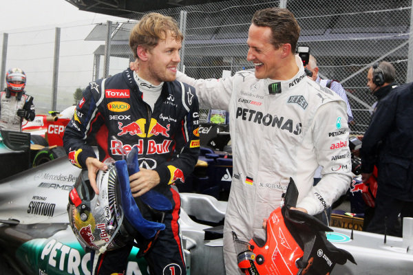 World Champion Sebastian Vettel (GER) Red Bull Racing celebrates in parc ferme with Michael Schumacher (GER) Mercedes AMG F1. Formula One World Championship, Rd20 Brazilian Grand Prix, Race, Sao Paulo, Brazil, 25 November 2012.  BEST IMAGE