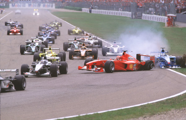 2000 German Grand Prix. Hockenheim, Germany. 28-30 July 2000. Mika Hakkinen leads David Coulthard (both McLaren MP4/15 Mercedes) as Michael Schumacher (Ferrari F1-2000) pulls across into Giancarlo Fisichella (Benetton B200 Playlife) on the approach to the Nordkurve at the start, resulting in a crash. World Copyright - Coates/LAT Photographic crash sequence 06. ref: 35mm A06.