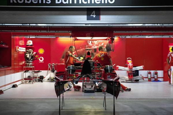 Mechanics work on Rubens Barrichello's Ferrari F2005 in the garage.